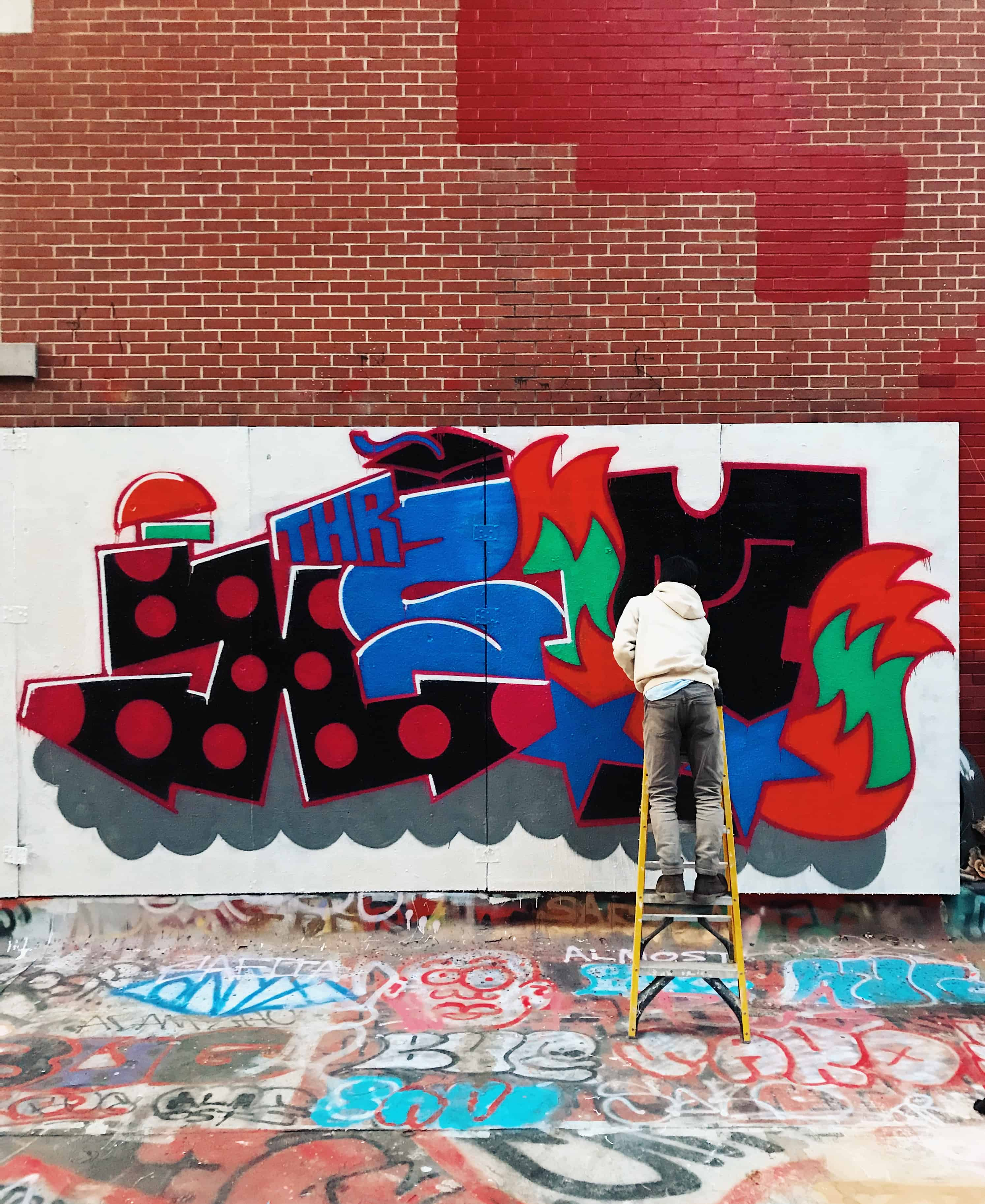 Graffiti artist painting on a NYC Chinatown rooftop.
