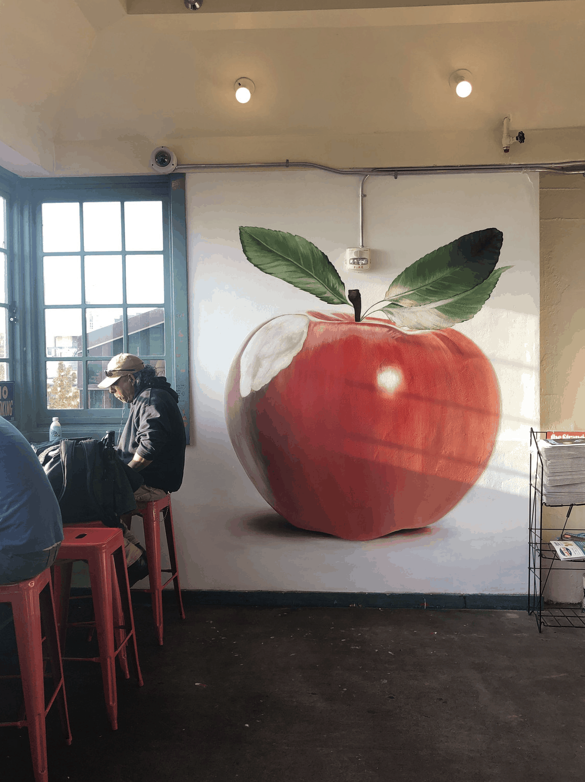 Mural of a realistically painted red apple inside a cafe in Seattle.
